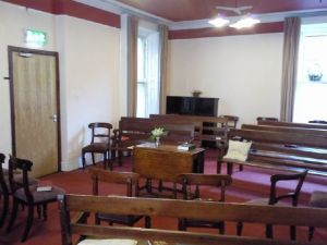 interior photo of Eustace Street Meeting House where Meeting for Worship takes place. Furnished with benches and chairs facing a table in the middle of the room.